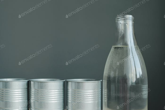 glass bottle and metallic flower pots still life