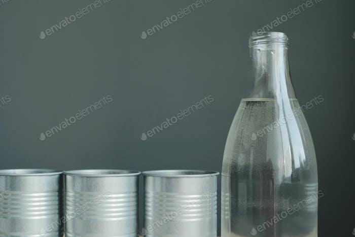 Glasflasche und metallische Blumentöpfe Stillleben