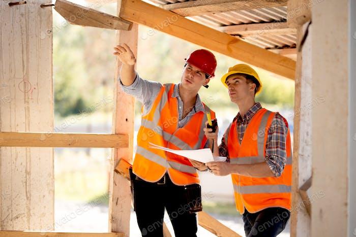Zwei Männer in Hemden, orangefarbene Arbeitswesten und Helme erforschen die Baudokumentation auf der
