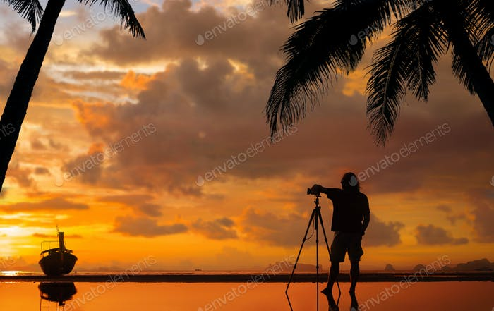 Silhouette of a photographer with tripod on beautiful tropical sunset
