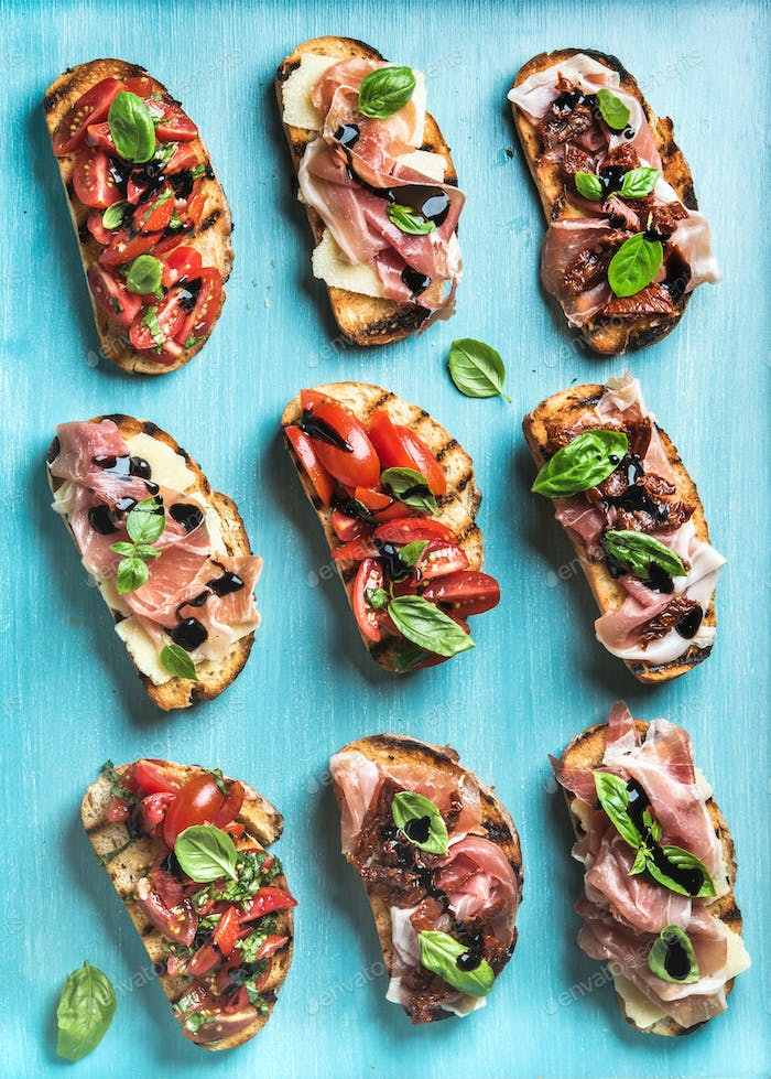 Brushetta set for wine. Variety of small sandwiches on turquoise blue backdrop, top view