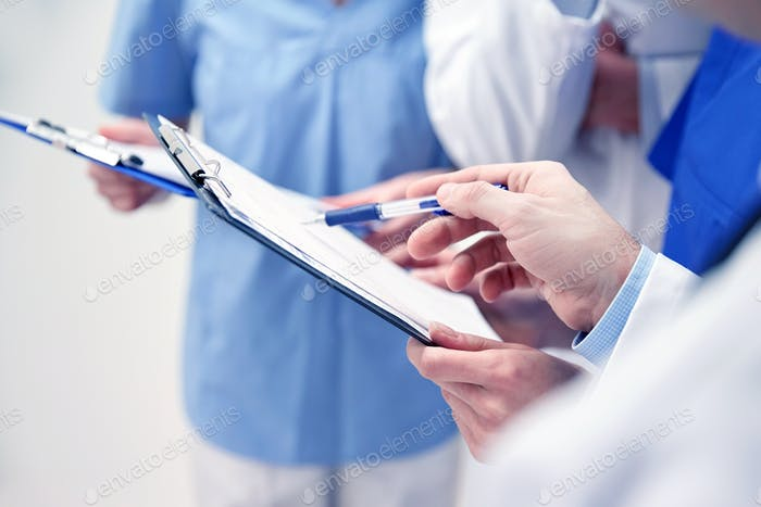 close up of doctors with clipboard at hospital