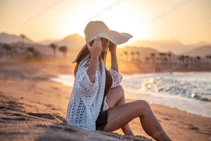 Beautiful boho model in a hat poses on the beach in the sun