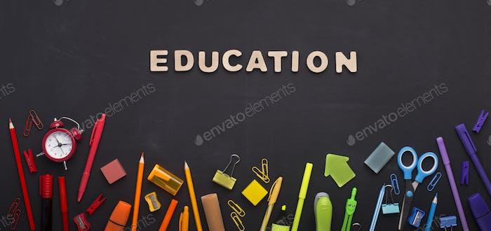 Rainbow of school supplies on chalk board background