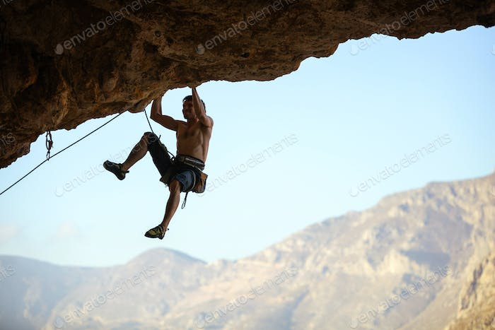 Young man struggling to climb ledge on natural cliff
