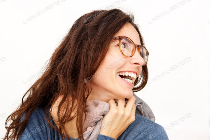 young woman with glasses and scarf laughing against white background