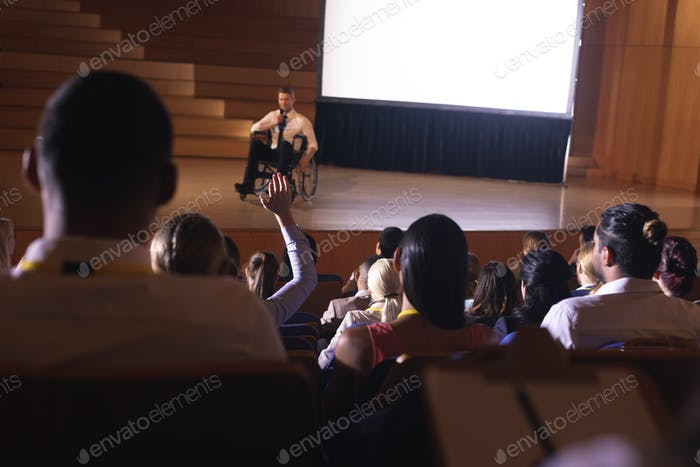 Businessman sitting on a wheelchair and giving presentation while the audience asking question