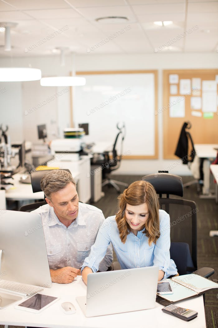Business colleagues working on laptop in office