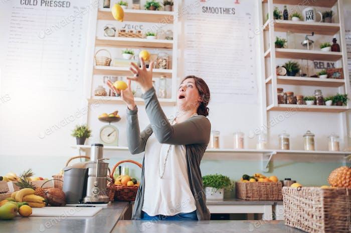 Junge Frau jonglieren mit Zitrone an Saftbar