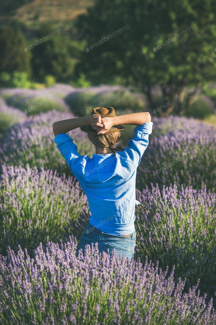 Young woman in straw hat enjoying lavender field, Isparta, Turkey