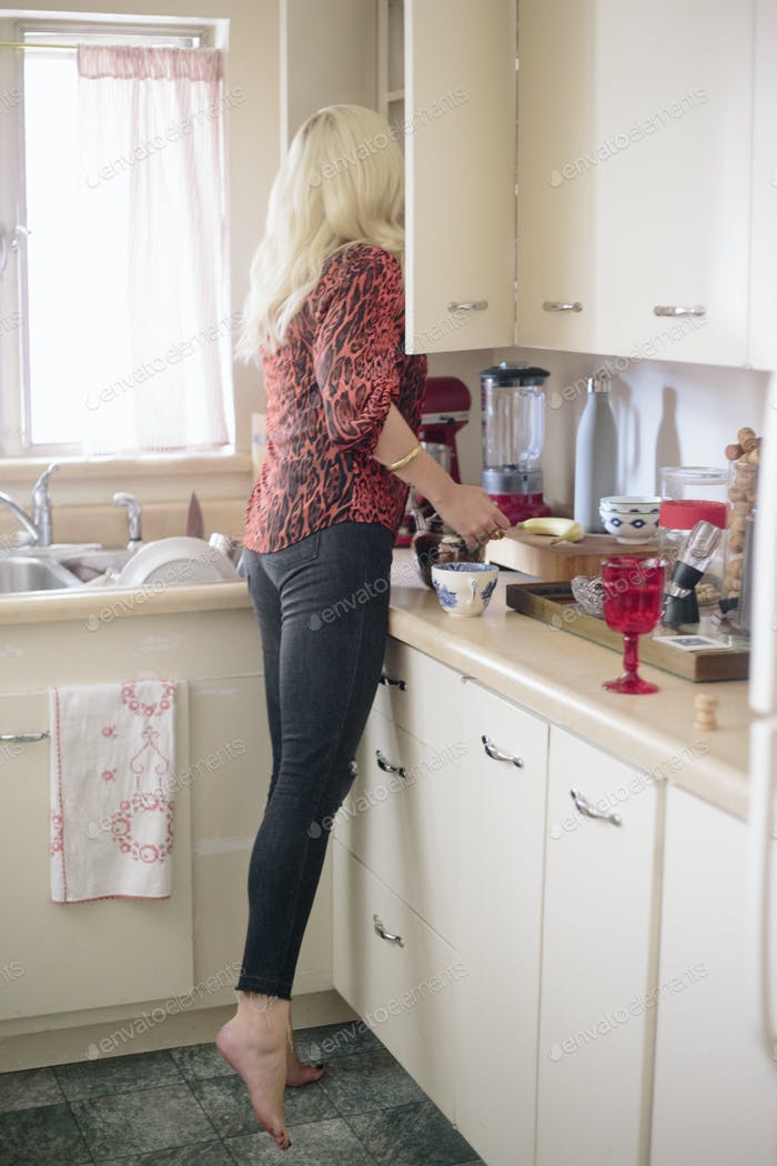 Blonde woman standing in a kitchen on tiptoes looking in a cupboard.