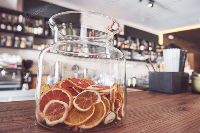 Getrocknete kandierte Orangen-, Kalk- und Zitronenscheiben in großem Glasbehälter mit Inhalt auch auf