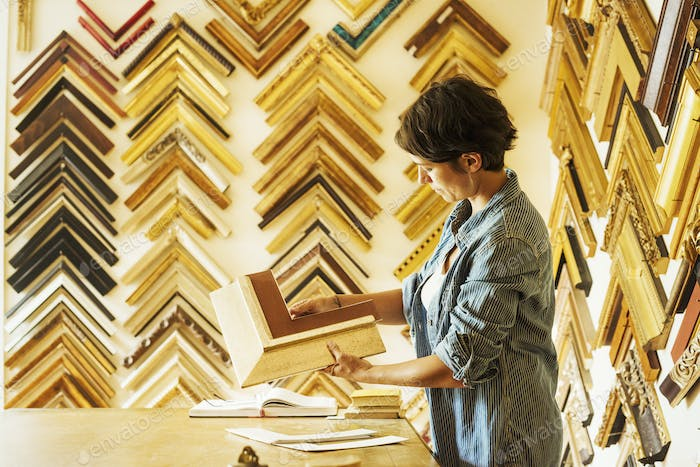 Woman working at a picture framers, a large selection of frames on the walls.