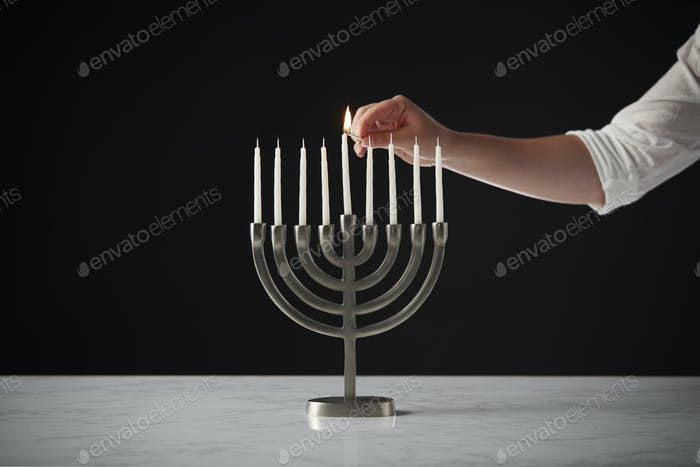 Hand Lighting Candle On Metal Hanukkah Menorah On Marble Surface Against Black Studio Background