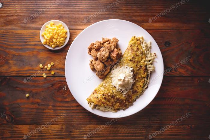 Mais CACHAPA mit Käse und gebratenem Schweinefleisch - Cochino Frito. Holzhintergrund, Draufsicht.