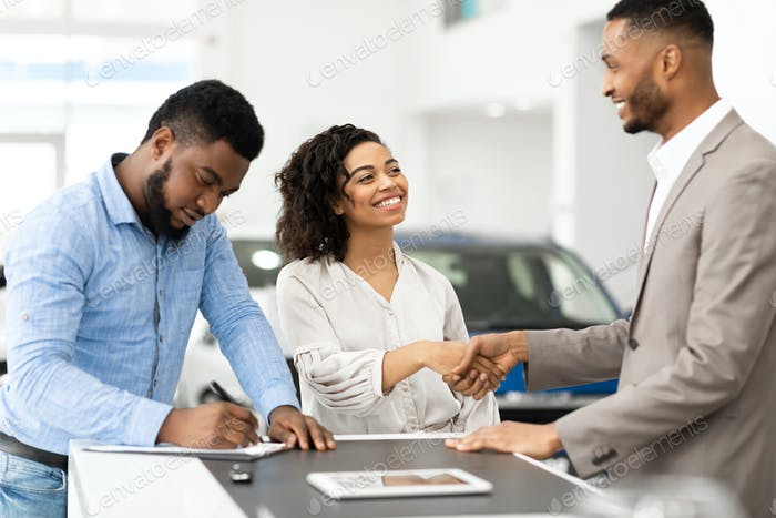 Couple Shaking Hands With Salesman In Cars Selling Center