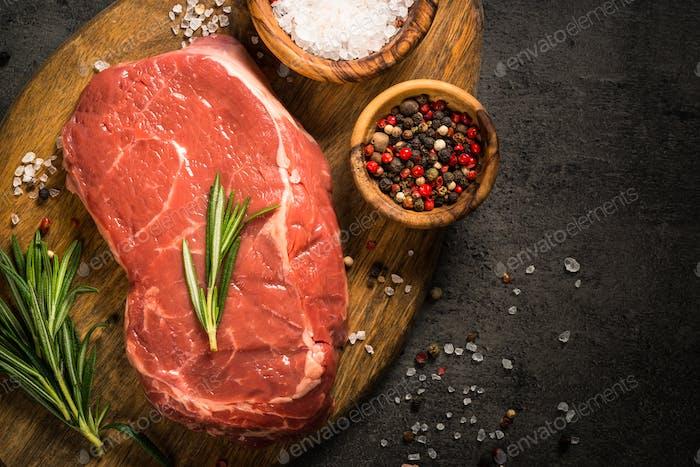 Fresh beef steak on black table