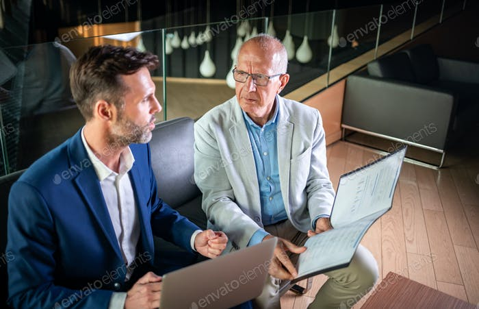 Businessman using laptop to discuss information with older colleague in modern business lounge