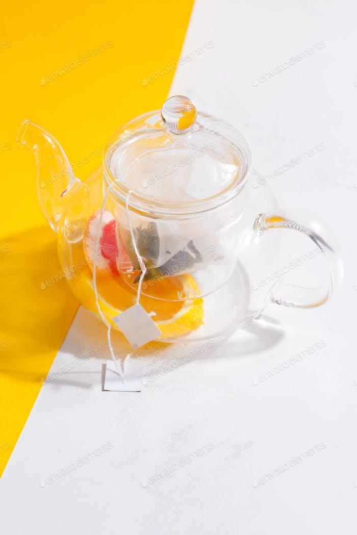 Summer homemade cold fruit tea drink in a glass transparent teapot on a duotone yellow white table
