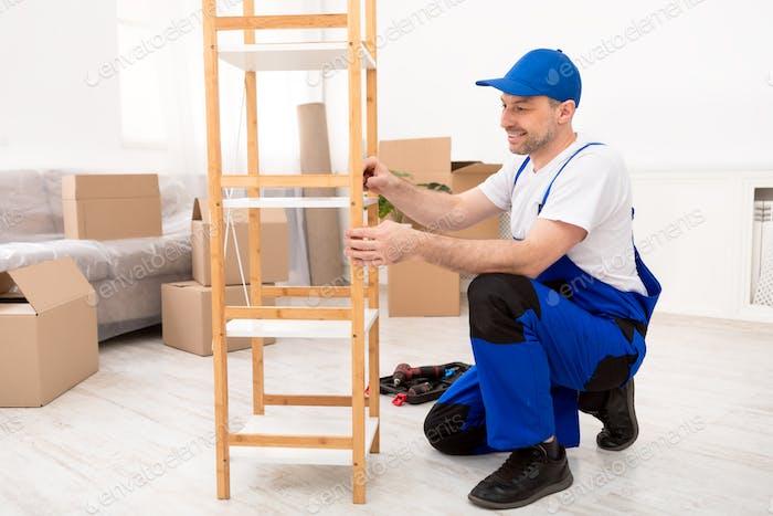 Repairman Installing Wooden Shelf Wearing Blue Coverall Working Indoor