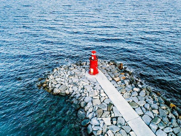 Aerial view of small red lighthouse in the blue sea