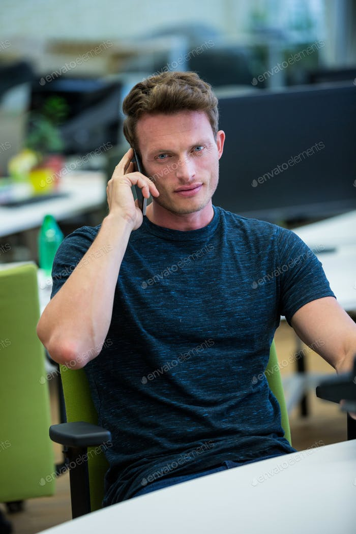 Male business executive talking on mobile phone in office