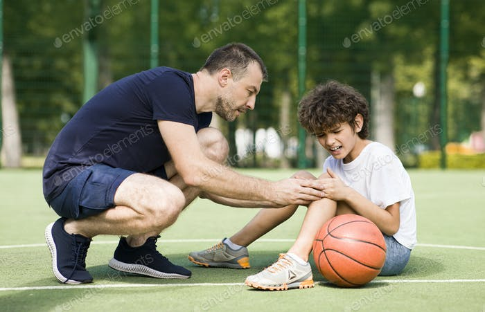 Lehrer helfen Junge mit Knietrauma nach dem Spielen Basketball
