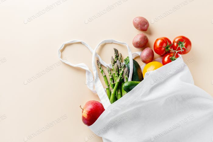 Different vegetables in textile bag on beige