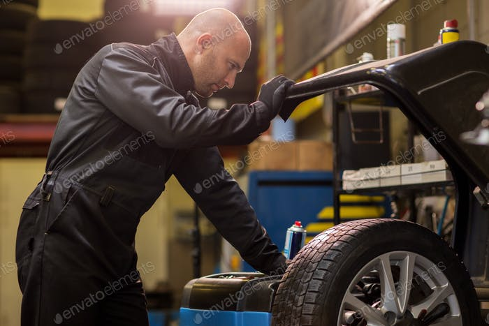auto mechanic balancing car wheel at workshop