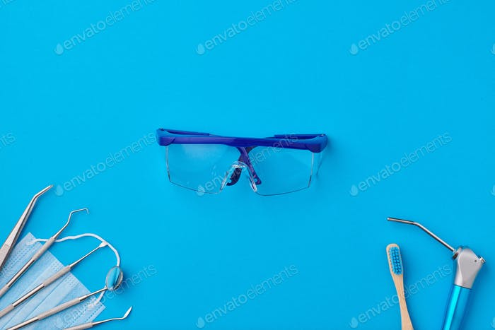 Dentist tools over blue background top view