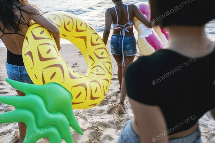 Group of diverse women walking at the beach with inflatable tube