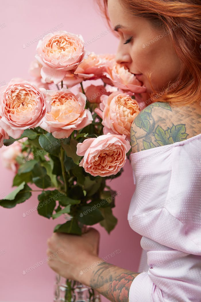 Pretty woman with ginger hair, tattoo on her shoulder and hands, holds bouquet of roses on a living