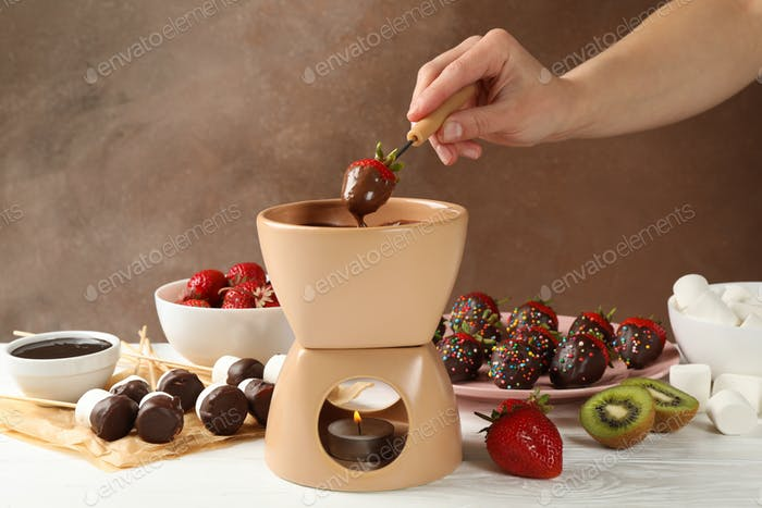 Woman dipping strawberry in chocolate. Delicious chocolate fondue