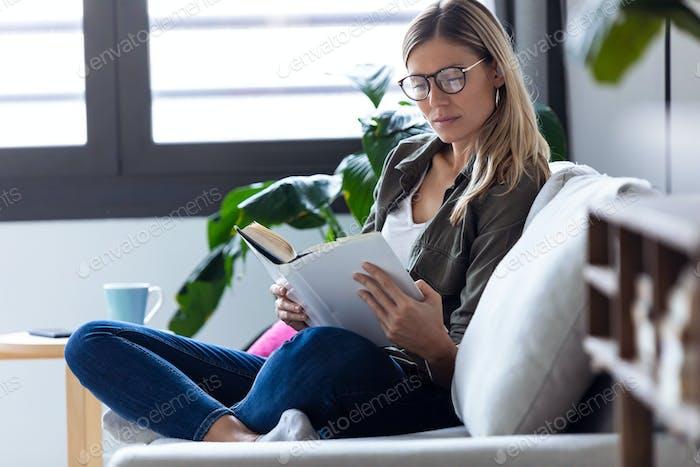 Mujer joven bonita leyendo un libro mientras se sienta en el sofá en casa.