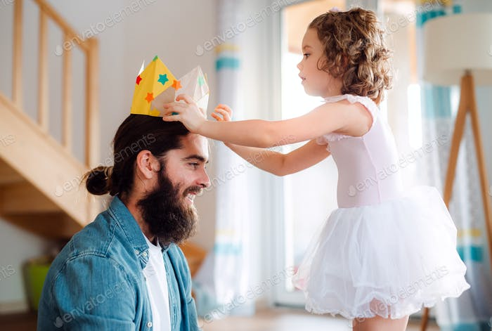 A small girl putting a paper crown on father's head at home when playing.