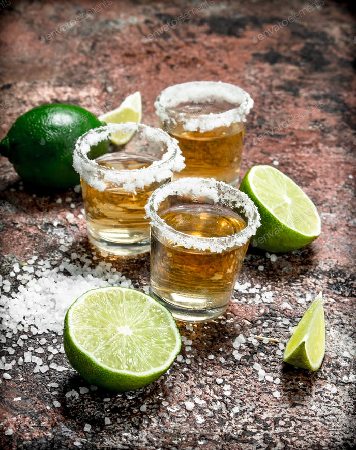 Tequila in a shot glass with salt and sliced lime.
