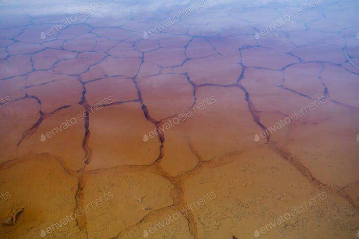 Poisonous water with cracked soil under it on abandoned toxic territory
