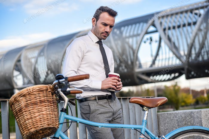 Business man standing by his vintage bicycle  drinking a coffee
