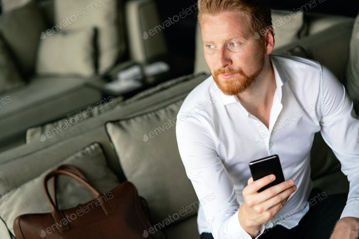 Young businessman sending message with mobile phone