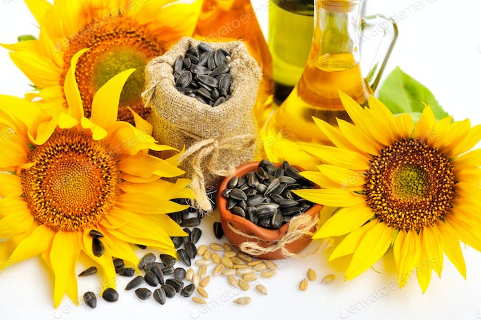 Yellow sunflowers with bottles of oil and a small bag of seeds o