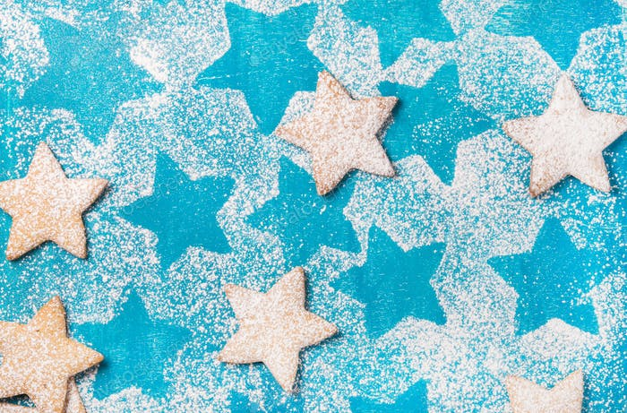 Heart shaped cookies with sugar powder over bright blue background