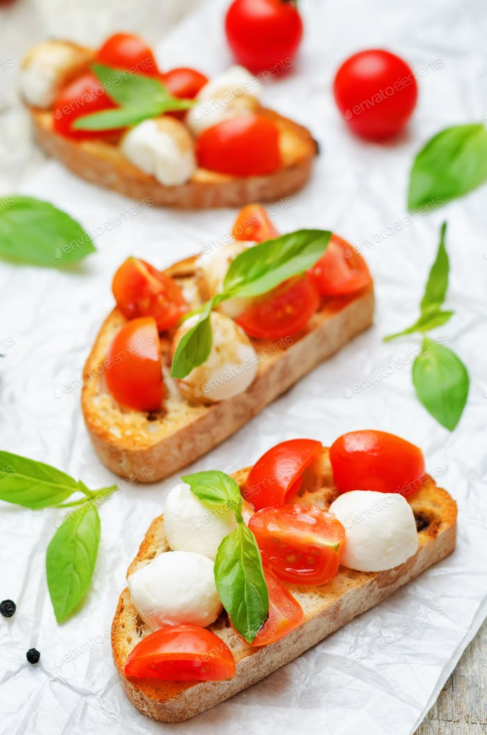 Caprese bruschetta with fresh tomatoes and Basil leaves