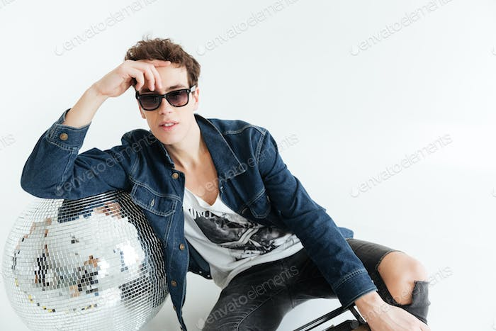 Young man near disco ball and boombox.