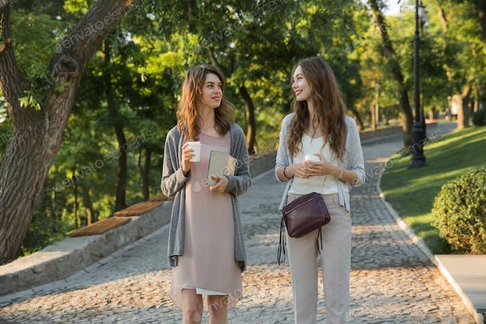 Alegre joven dos Mujeres caminando al aire libre en Parque bebiendo café