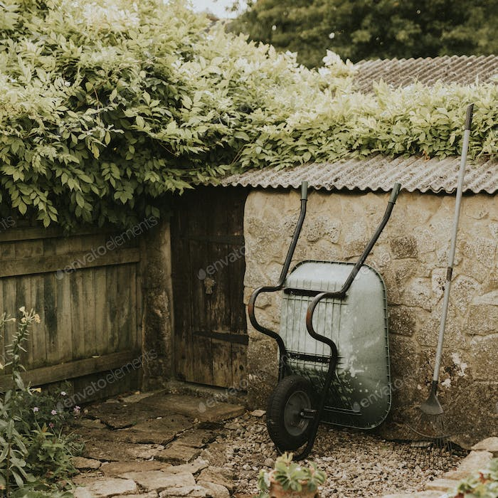 Wheelbarrow leaning on a garden shed