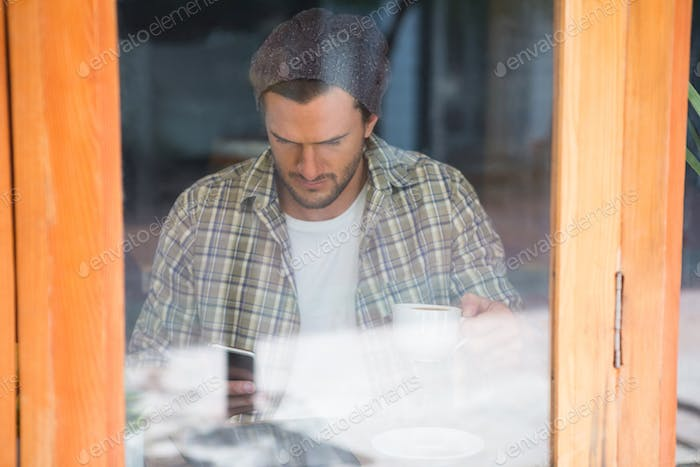 Man using mobile phone in cafe seen through window