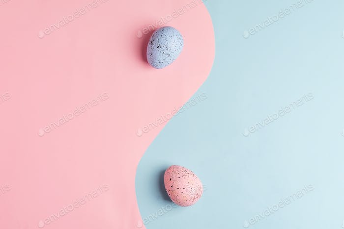 Two handmade Easter painted eggs on a duotone pastel colored background as a symbol of yin and yang