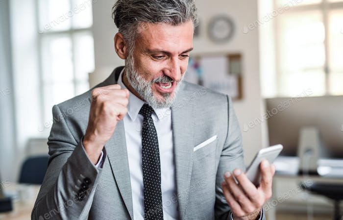 Mature businessman with smartphone standing in an office, expressing excitement.