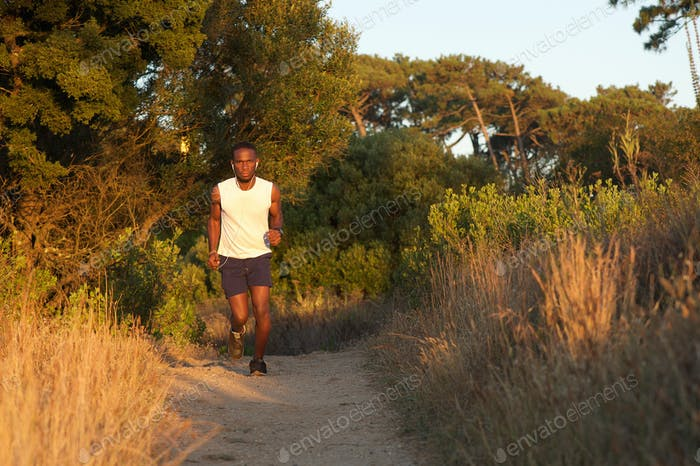 Fit young man running on path outdoors