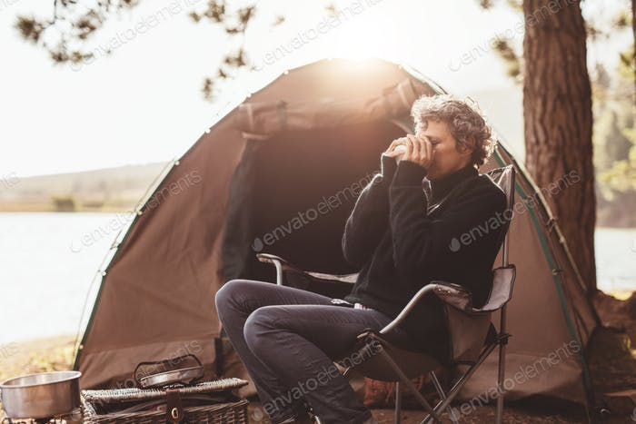 Mature woman at campsite drinking coffee